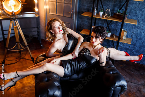 Foto op Plexiglas Artist KB two beautiful girls in black leather dresses in a luxirious chair in a studio. two vocalists.