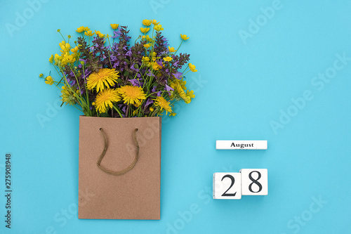 Fotografia  Wooden cubes calendar August 28 and field colorful rustic flowers in craft package on blue background