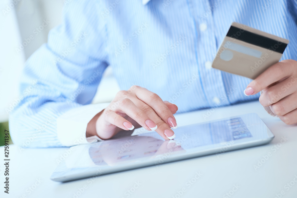 Fototapety, obrazy: Close-up woman's hands holding a credit card and using tablet pc for online shopping. Middle section of young businesswoman making online payments with credit card and tablet.