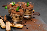 Classic tiramisu dessert in a glass and savoiardi cookies on dark concrete background