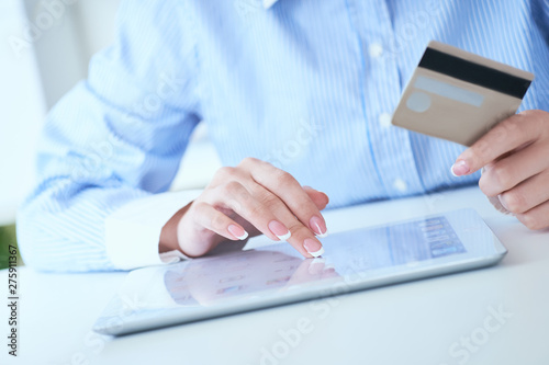 Close-up woman's hands holding a credit card and using tablet pc for online shopping. Middle section of young businesswoman making online payments with credit card and tablet.