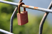 Red Padlock On Fence With Engr...