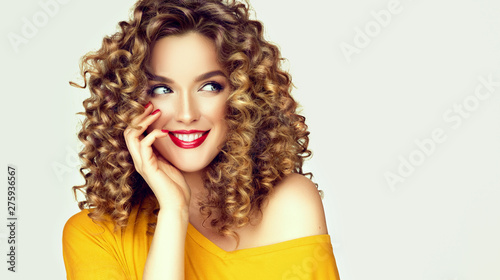 Photo Stands Height scale Woman surprise showing product with cunning look .Beautiful girl with curly hair looking away . Presenting your offer. Isolated on white background. Expressive facial expressions