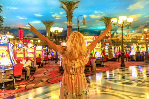 Poster de jardin Las Vegas Happy winning caucasian woman at the casino of Las Vegas, Nevada, USA. Blonde lady enjoying spending money and being lucky enough to win. Architecture blur background. Gambling addict concept.