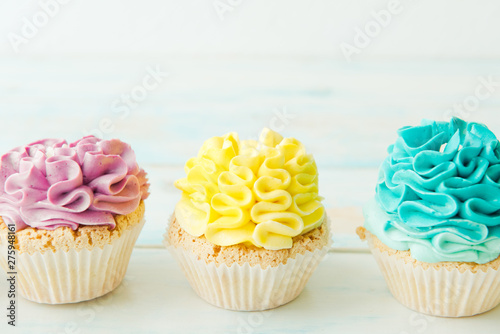 Photo  Three colorful cupcakes on a light background. Copy space