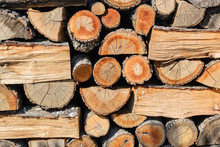 Background Of Ends Of Logs And Dry Firewoods. Close-up  Of Outdoor Stack Of Wood On A Sunny Day. Folded And Packaged Firewood. Woodpile.