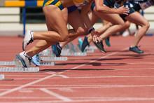 Group Of Female Track Athletes On Starting Blocks