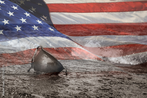 Valokuva United States Flag with Black and White photo of military helmet on beach in the water
