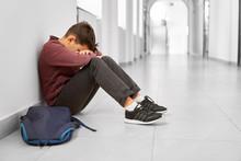 Sad School Boy Sitting Alone O...