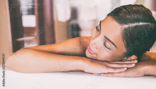 Wall Murals Equestrian Luxury spa massage Asian woman relaxing lying down on table at hotel room. Massage therapy skincare beauty treatment.