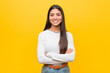 Leinwandbild Motiv Young pretty arab woman against a yellow background who feels confident, crossing arms with determination.