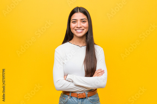 Canvastavla  Young pretty arab woman against a yellow background who feels confident, crossing arms with determination