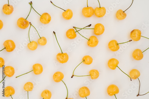 Fotomural  Fresh yellow cherries scattered over white background, top view