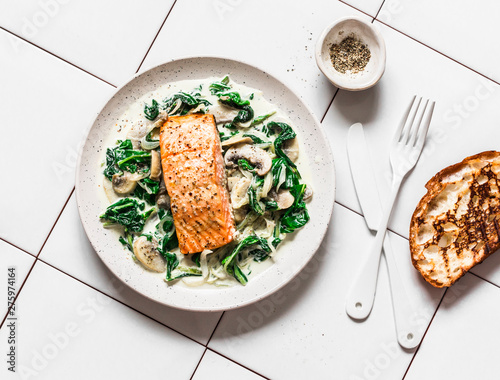 Fotografía Roasted salmon with creamy spinach mushrooms sauce on a light background, top view
