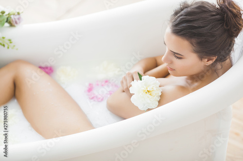 Foto Perfact woman bathing with flowers and milk