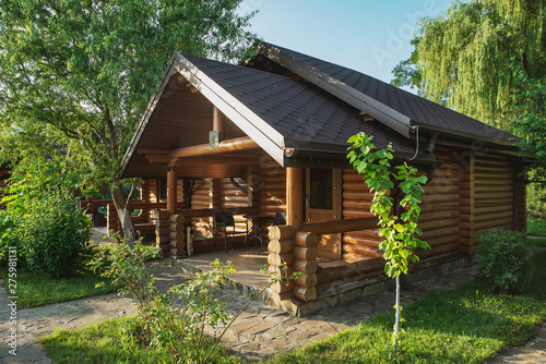 Wooden cottages with log and paved with wild stone paths on the background of green trees and flowering shrubs