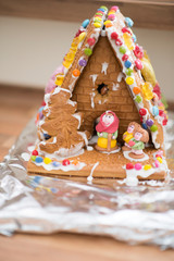 homemade gingerbread house with witch and Hansel and Gretel in front of it
