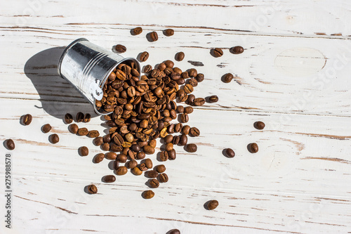 Wall Murals Coffee beans Coffee beans spilling out of a bucket, on a white wooden background, top view
