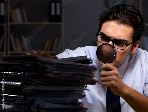 Fotobehang Hoogte schaal Young businessman working overtime late in office
