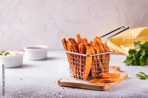 Homemade baked sweet potato french fries with ketchup, salt on wooden board with Fototapet