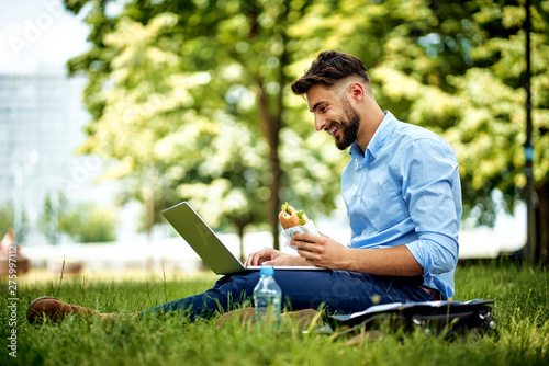 Fotografía Young cheerful businessman sitting in the park with sandwich and laptop