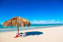 A Sun Lounger With Red Towel Under An Umbrella On The Sandy Beach By The Sea And Cloudy Sky. Vacation Background. Idyllic Beach Landscape. Free Space For Your Text