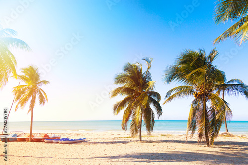 Photo  The tropical beach of Varadero in Cuba with sailboats and palm trees on a summer day sunset with turquoise water