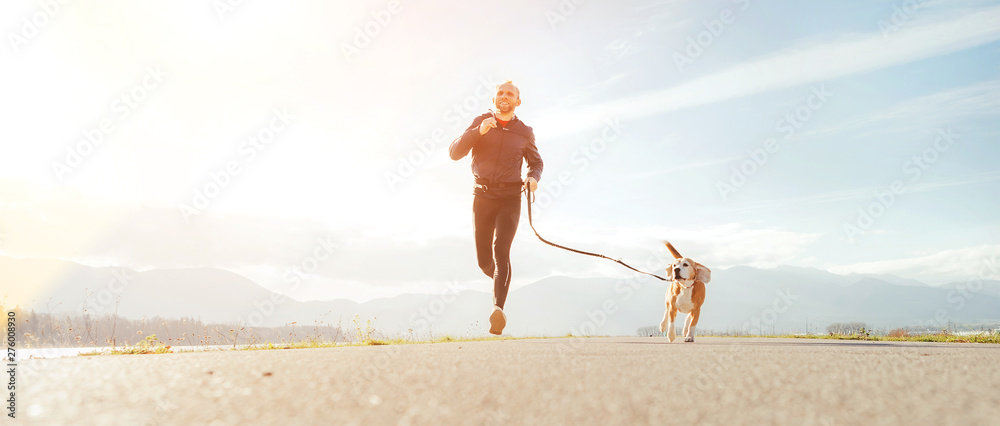 Fototapety, obrazy: Jogging man with his dog in the morning. Active healthy lifestyle concept image.