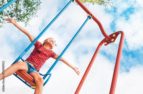Funny smiling little girl swinging on the swing wide opened an arms with blue sky background