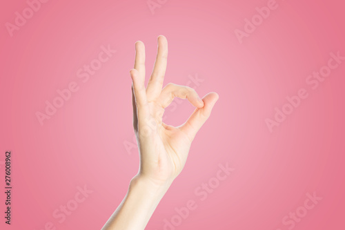 Positive gesture on a pink background. Hand show okay sign, close up - 276008962