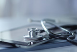 Medical equipment: blue stethoscope and tablet on white background. Medical equipment - 276010799