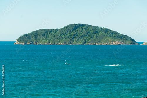 Photo Vista do alto de um rochedo para o mar e uma ilha deserta florestada ao horizonte