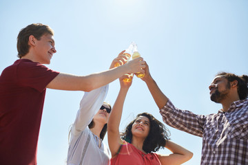 Low angle portrait of friends clinking beer bottles against blue sky in Summer, copy space