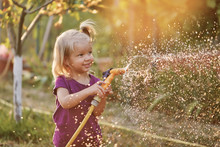Cute Little Girl Watering Flowers In The Garden At Summer Day. Child Using Garden Hose On Sunny Day. Mommys Little Helper.