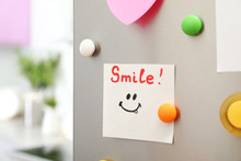 """Note With Word """"Smile"""" And Colorful Magnets On Refrigerator Door In Kitchen. Space For Text"""