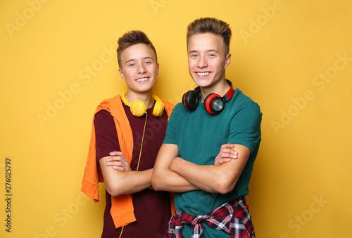 Teenage twin brothers with headphones on color background Wallpaper Mural