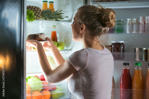 Beautiful young woman choosing food in refrigerator at night Wallpaper Mural