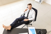 Carefree Businessman Talking By Mobile Phone In Office