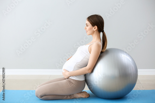 Fotomural  Beautiful pregnant woman with fitball training near grey wall
