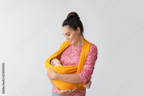 Young mother with little baby in sling on light background Wallpaper Mural