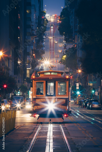 Classic view of historic traditional Cable Cars riding on famous California Street at night with city lights, San Francisco, California, USA Wall mural