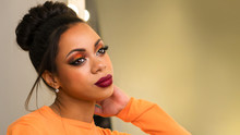 Portrait Of Attractive Afro American Young Woman With Fashion Luxury Makeup Orange-coloured Shades And Her Hair Scraped Back Into High Bun. Perfect Skin. Long Eyelashes. Big Lush Beautiful Lips. Beaut
