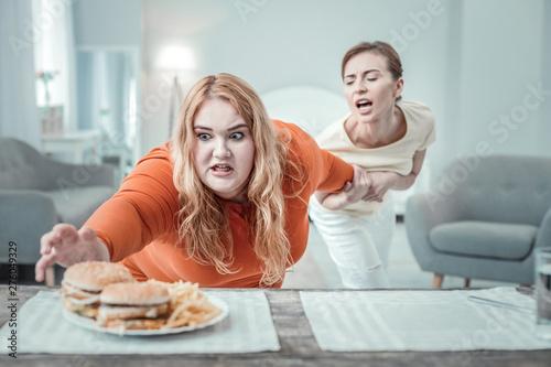 Crazy plump female person catching soft hamburger
