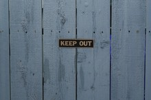 A Keep Out Sign On A Blue Wood...