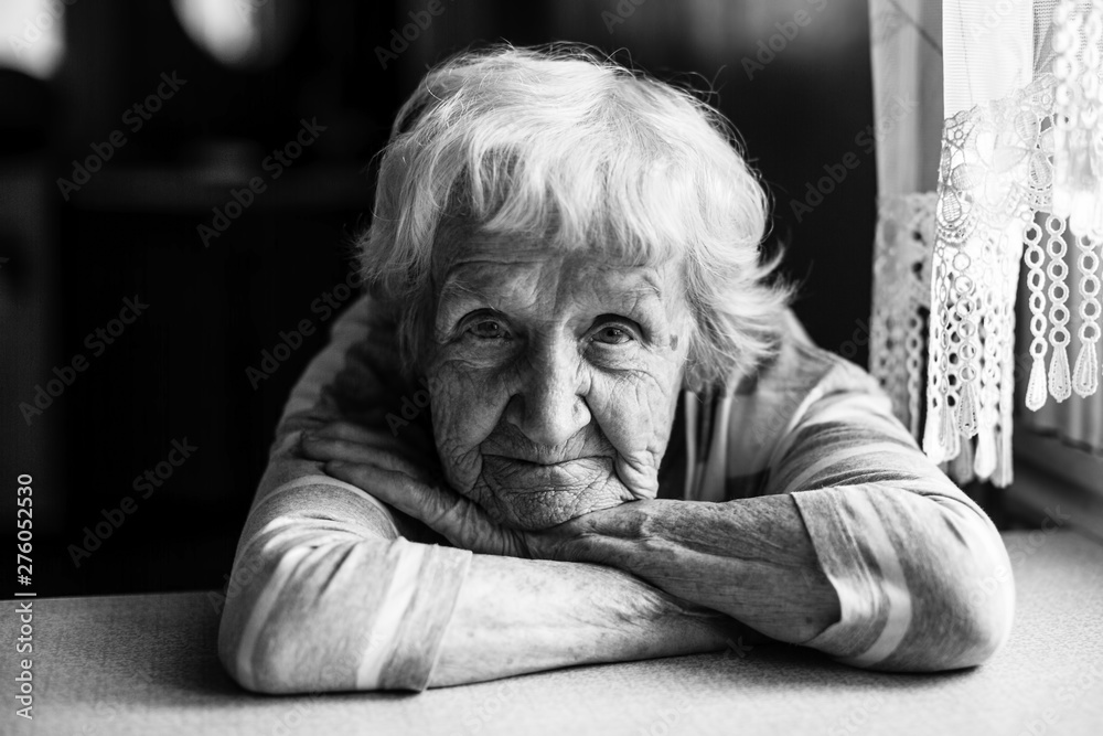 Fototapety, obrazy: Close-up black and white portrait of a old woman at the table in home.