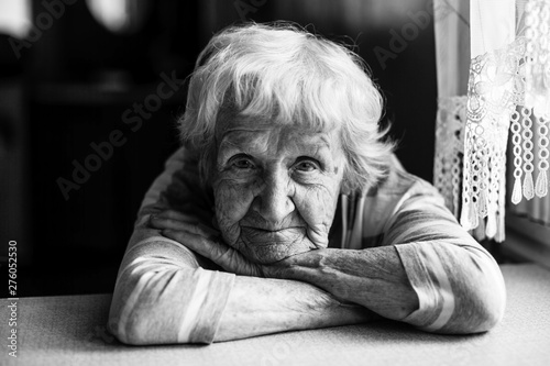 Obraz Close-up black and white portrait of a old woman at the table in home. - fototapety do salonu