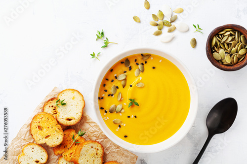 Valokuvatapetti Diet autumn pumpkin or carrot cream soup in bowl served with seeds and crouton on stone table from above