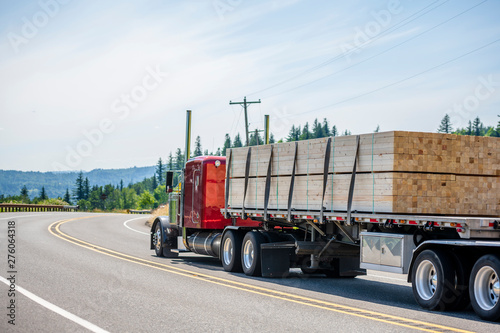 Photo  Red big rig semi truck transporting wood lumber on the flat bed semi trailer run
