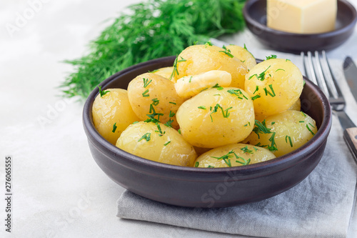 Fotografia New young boiled  potato topped with melted butter and chopped dill in ceramic b