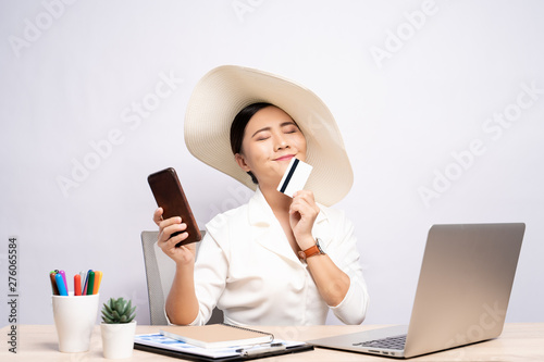 Photo Woman wearing hat use smart phone and credit card at office isolated over backgr